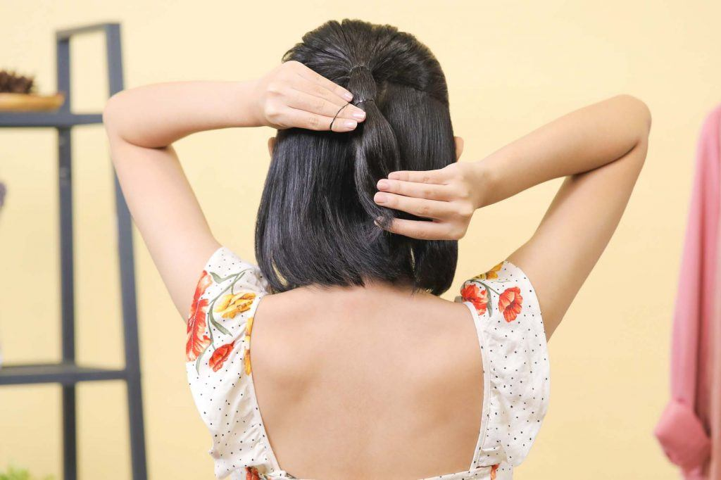 ผู้หญิงเอเชียผมสั้นสีดำหน้าม้าตรง กำลังมัดผม