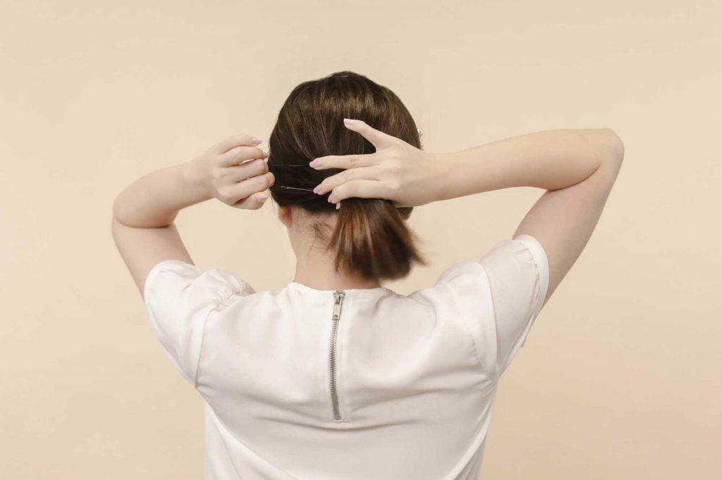 ผู้หญิงเอเชียผมสั้นสีดำ กำลังมัดผม