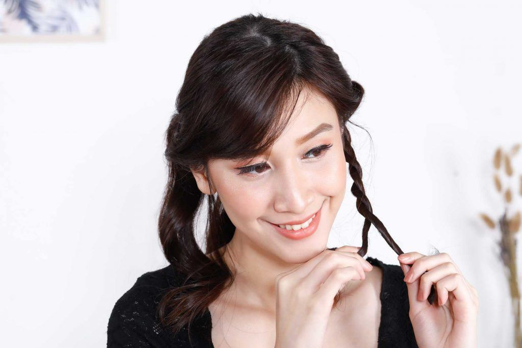 ผู้หญิงเอเชียผมยาวสีดำ กำลังถักเปีย