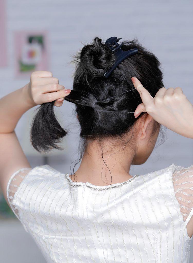 ผู้หญิงเอเชียผมหยักศกยาวประบ่า เกล้าผมมวยต่ำ