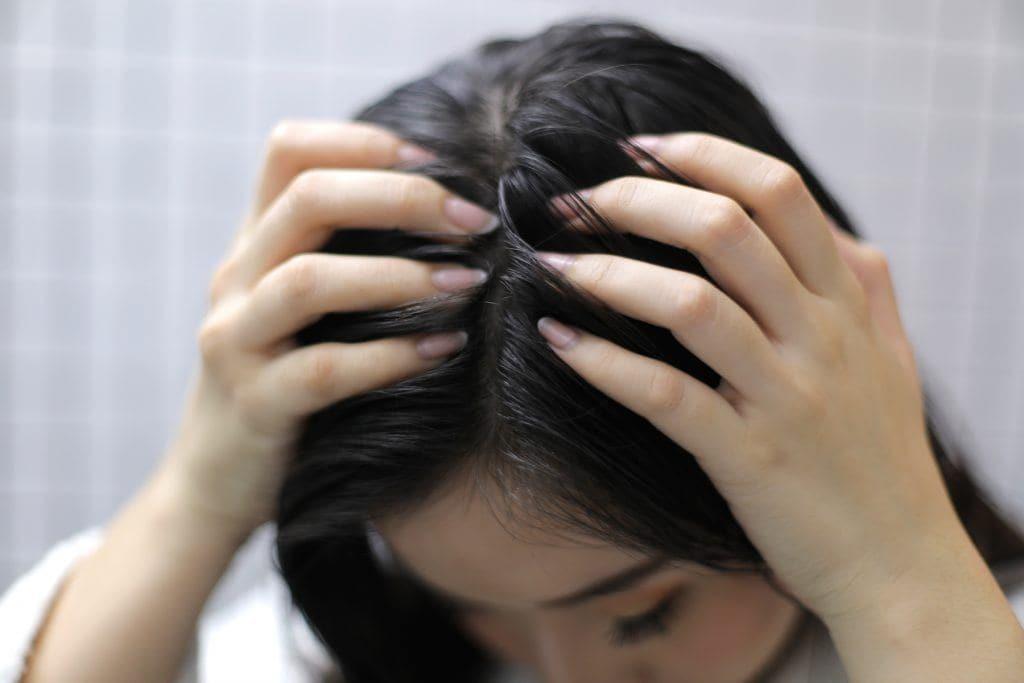 ผู้หญิงเอเชียผมยาวสีดำ กำลังนวดหนังศีรษะ