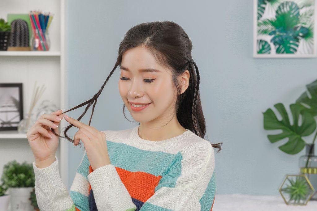 ผู้หญิงเอเชียผมยาวสีดำ กำลังถักเปียเส้นเล็กๆ