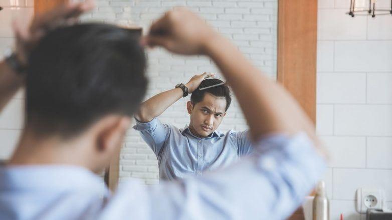 ผู้ชายกำลังตัดผมเองหน้ากระจก