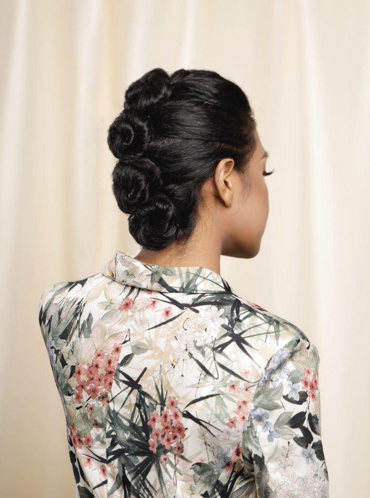 ผู้หญิงเอเชีย ไว้ผมยาวหยิก สีดำ รวบผมด้านหลังขดเป็นวง